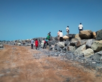 The District Chief Executive and Members of the District Statutory Committee inspecting the Progress of the Sea Defence Wall at Adjoa.